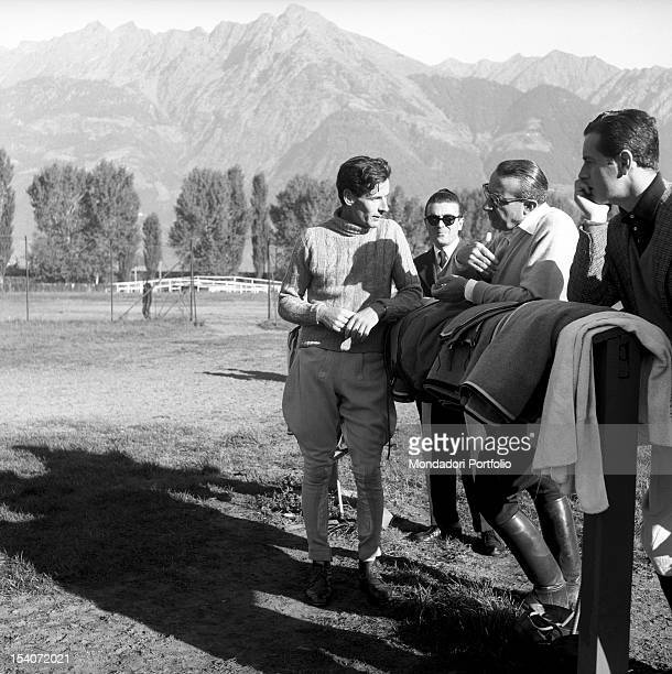 The British colonel and pilot Peter Townsend talk with other men during an equestrian competition. Merano, 1955