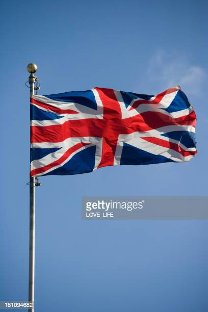 The British flag flying high on top of a flagpole