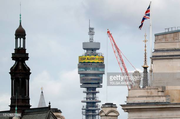 """The British Government's new COVID-19 slogan """"Stay Alert, Control the Virus, Save Lives"""" is pictured on the BT tower, in central London on May 13 as..."""
