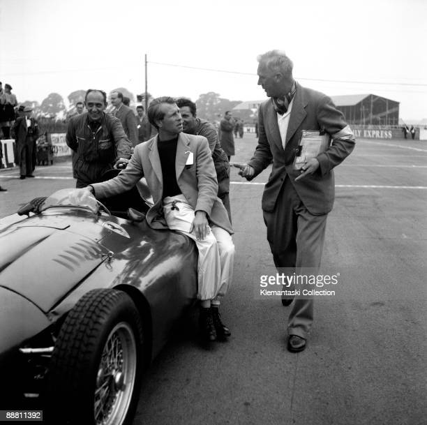 The British Grand Prix Silverstone July 14 1956 Peter Collins sits on the side tanks of his FerrariLancia D50 as the mechanics push the car to the...