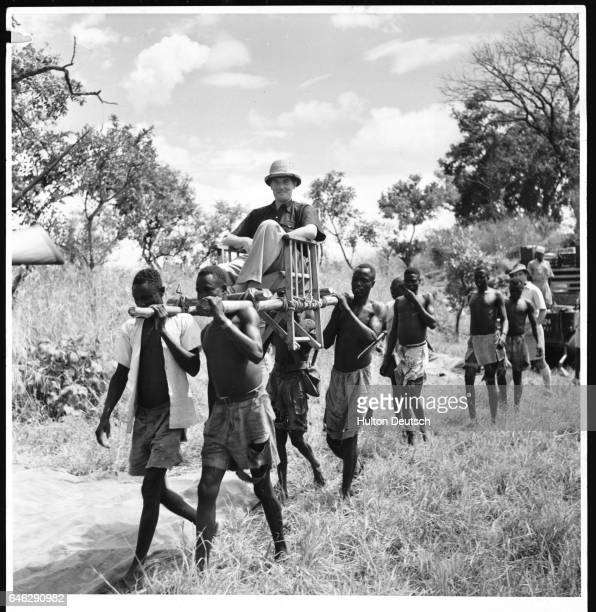 The British journalist Kenneth Allsop is carried in a sedan chair by a group of men in the Sudan 1952