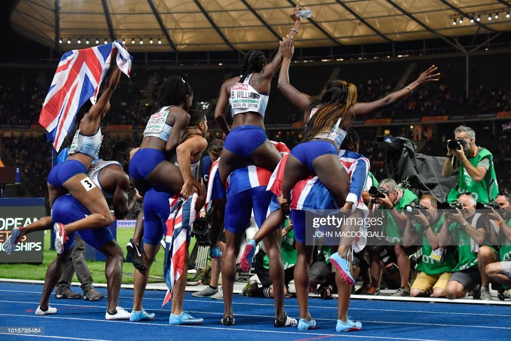 The British men's and women's 4x100m relay teams pose for photographers after the men's 4x100m relay final during the European Athletics Championships at the Olympic stadium in Berlin on August 12, 2018.