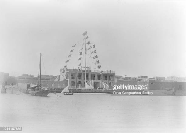 The British Political Agency in Kuwait, This image shows a building on the sea front covered in flags, with a dhow boat in the foreground, Kuwait, 22...