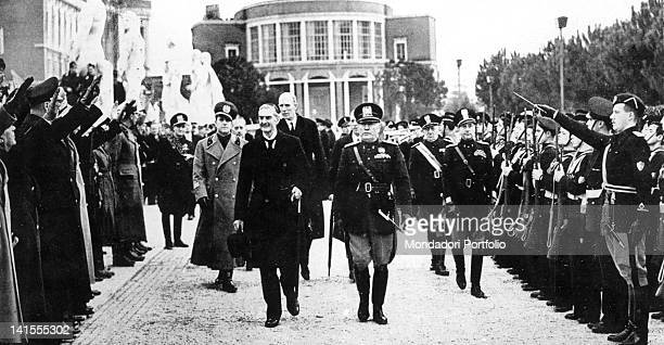The British Prime Minister Neville Chamberlain and Benito Mussolini arriving at the Stadio dei Marmi in Rome, greeted by young members of the...
