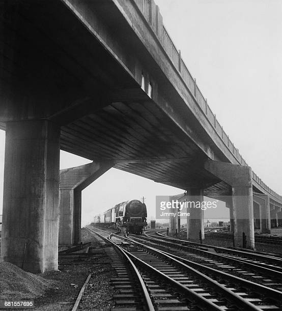 The British Railways Coronation Class 462 passenger steam locomotive the MidDay Scot passes under the newly constructed 1385 feet long Bletchley rail...