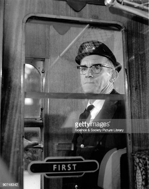 The British Railways' porter is looking out of the window of a First Class carriage