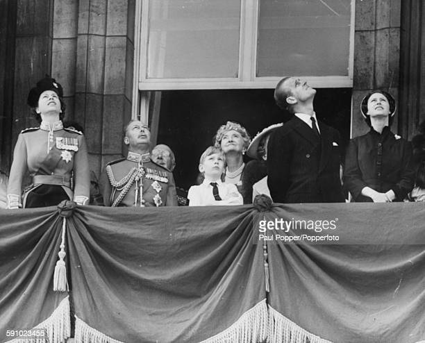 The British Royal Family look up from the balcony of Buckingham Palace to view a fly past of Royal Air Force planes following the trooping of the...