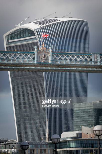 The British Union Jack flag flies from the highlevel walkway of the Victorianera Tower Bridge near the modern Walkie Talkie building on 14th...