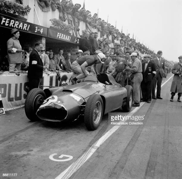 The Britsh Grand Prix Silverstone July 14 1956 Alfonso de Portago leaps into the car he was taking over from Eugenio Castellotti who is removing his...