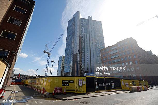The Broadgate Tower stands beyond hoardings surrounding the construction site of Principal Place, a joint development by Brookfield Property Partners...