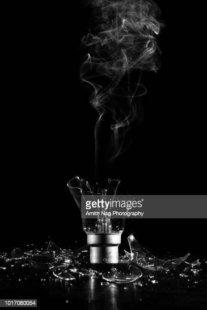 the broken bulb with smoke from filament - smoking crack stock photos and pictures