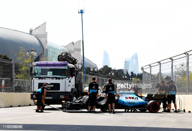 The broken car of George Russell of Great Britain and Williams is pushed down the pitlane after stopping on track during practice for the F1 Grand...