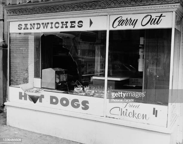 The broken window of a cafe selling sandwiches, hot dogs and fried chicken in Washington, DC, during the widespread riots which following the...