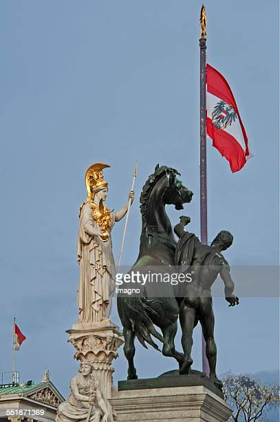 The bronze statues of horse tamers on the ramp of the Vienna Parliament Right the Pallas Athene of the Pallas Athena fountain Vienna 2013 Photograph...