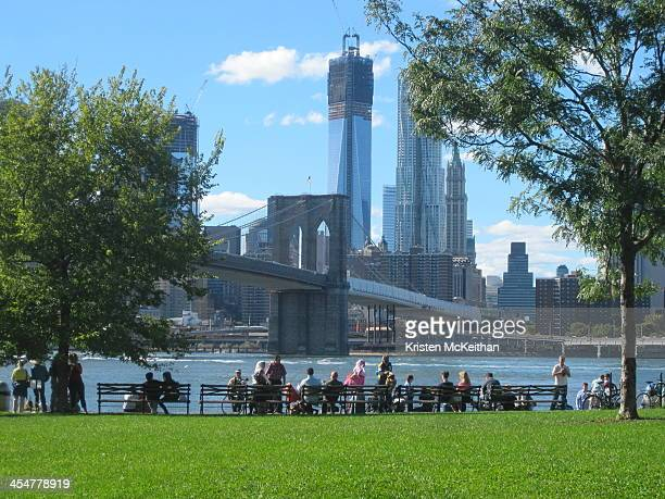 CONTENT] The Brooklyn Bridge Park waterfront benches in Dumbo Brooklyn New York on a sunny day The photo captures many different types of visitors...