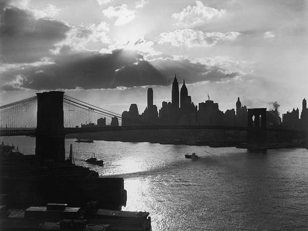The Brooklyn Bridge silhouetted against the Manhattan...