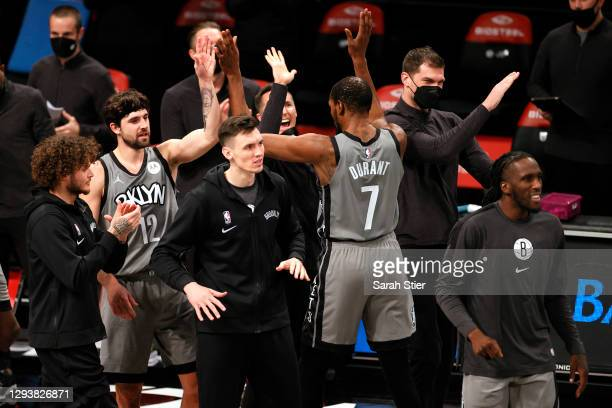 The Brooklyn Nets bench high-fives Kevin Durant after the second half against the Atlanta Hawks at Barclays Center on December 30, 2020 in the...