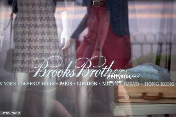 The Brooks Brothers logo is painted on the window of a store in closed along the Magnificent Mile on July 08, 2020 in Chicago, Illinois. The retailer...