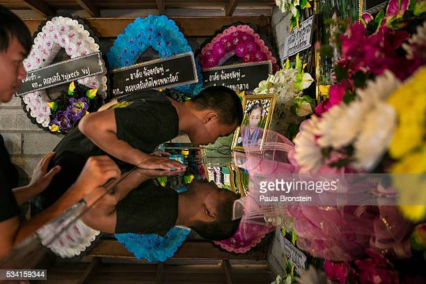 The brother of Chomphu age 8 peers into her coffin during a memorial service in the Hmong community of Jom Thong Chiang Mai province May 25 2016 A...