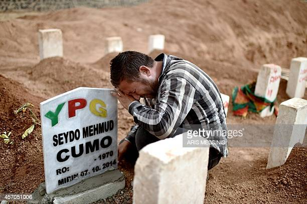 The brother of Syrian Kurdish People's Protection Units militant Seydo Mehmud mourn above his grave on October 11, 2014 in the Turkish town of Suruc,...