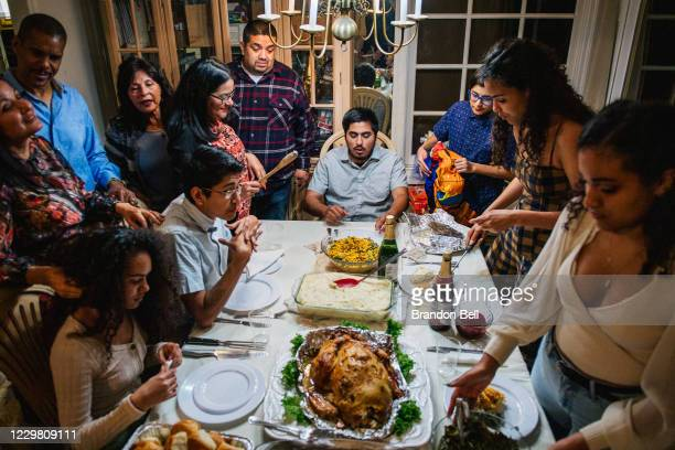 The Broughton family prepares for their dinner prayers during a gathering on November 26, 2020 in Los Angeles, California. Families have adjusted...