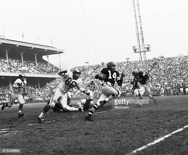 The Browns Otto Graham makes approximately 40 yards on the ground after fading back to pass and being rushed decided to run Eagles Norm Willey makes...