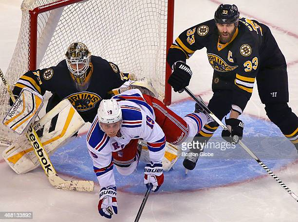 The Bruins' Zdeno Chara clears the Rangers' Jesper Fast from the front of the Bruins net in the third period as Bruins goalie Niklas Svedberg has a...