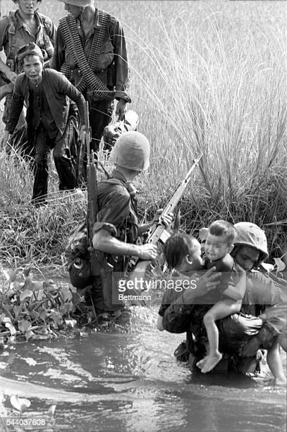 The brutality and heartlessness of the war here can be seen in this photo of a Marine carrying two crying orphaned Vietnamese children across a swamp...