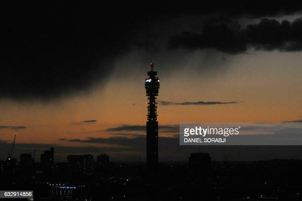The BT Tower is seen at sun set as dark clouds gather on the horizon in London on January 28 2017 BT shares dived by a fifth on January 24 2017 after...