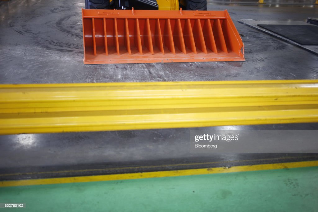 The bucket of a skid steer loader construction vehicle is seen on the floor of the JC Bamford Excavators LTD. (JCB) manufacturing plant in Pooler, Georgia, U.S., on Friday, Aug. 11, 2017. The Federal Reserve is scheduled to release industrial production figures on August 17. Photographer: Luke Sharrett/Bloomberg via Getty Images