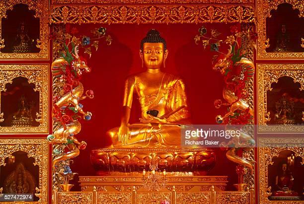 The Buddha seen as part of a shrine in the prayer room of Kagyu Samye Ling Buddhist retreat centre in Eskdalemuir, Scotland. A Buddhist shrine...