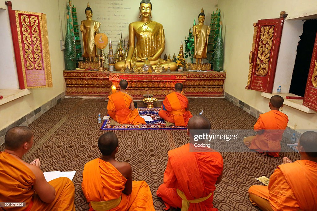 Group of seated, young Buddhist monks chanting and reading prayers at a ceremony. : News Photo