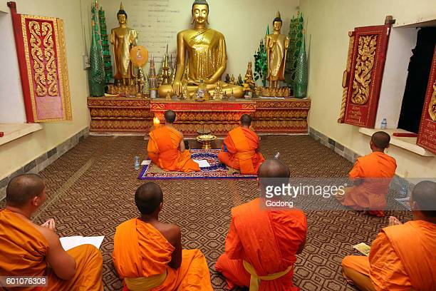 the Buddhist temple's most sacred complex Group of seated young Buddhist monks chanting and reading prayers at a ceremony Vang Vieng Laos