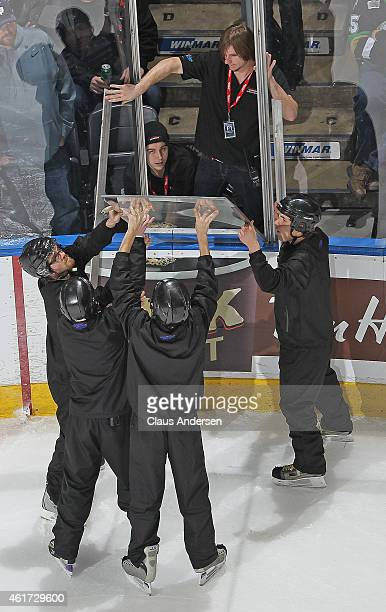 The Budweiser Gardens ice crew replace a pane of glass during a play stoppage between the Sarnia Sting and the London Knights in an OHL game at...
