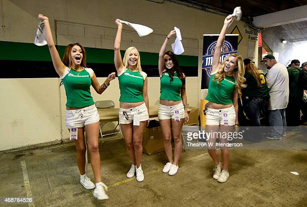 The Budweiser Girls greet fans as they enter the stadium before the start of the game between the Texas Rangers and Oakland Athletics on Opening Day...