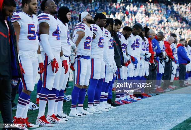 The Buffalo Bills stand for the national anthem prior to the game against the New England Patriots at Gillette Stadium on December 23 2018 in...