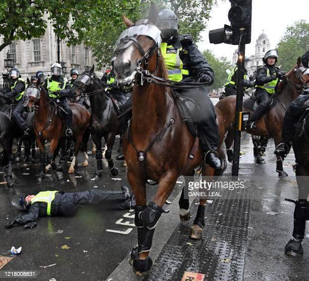 The bulb from a broken traffic light shines as a mounted police officer lays on the road after being unseated from their horse on Whitehall, near the...