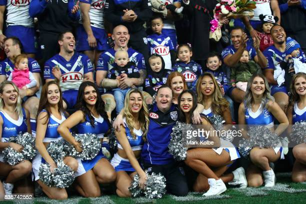 The Bulldogs club members cheer on stage as Bulldogs team assistant Sean White poses with cheergirls after a presentation to the players leaving the...