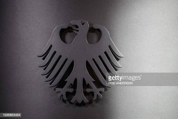"""The """"Bundesadler"""" , the coat of arms of Germany, is pictured on a speaker's lectern at the Interior Ministry in Berlin on September 19, 2018 in..."""
