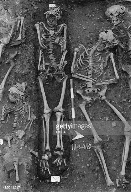 The burial of a male aged 26–35 years in a charcoallined coffin in the large mass burial trench from the Black Death cemetery East Smithfield London...