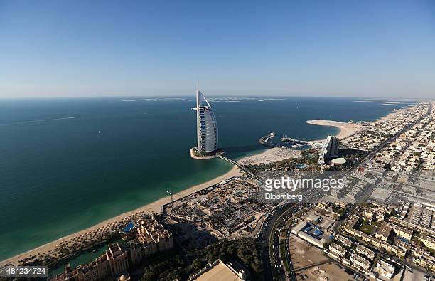 The Burj Al Arab luxury hotel center stands offshore near the Jumeirah Beach hotel right on the waterfront in Dubai United Arab Emirates on Tuesday...