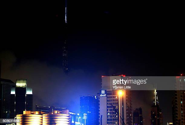 The Burj Khalifa is surrounded in smoke after a fire engulfed the nearby Address Downtown Hotel on December 31 2015 in Dubai United Arab Emirates