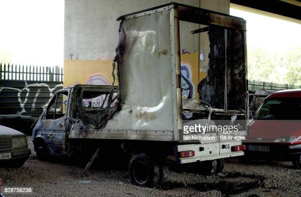The burned out wreck of a box van which is believed to have been used by the killers of delivery lorry driver Ian Jones is examined by a police...