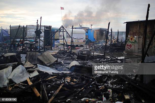 The burnt Jungle camp smoulders on October 26 2016 in Calais France Overnight fires broke out in many parts of the camp destroying shacks and...