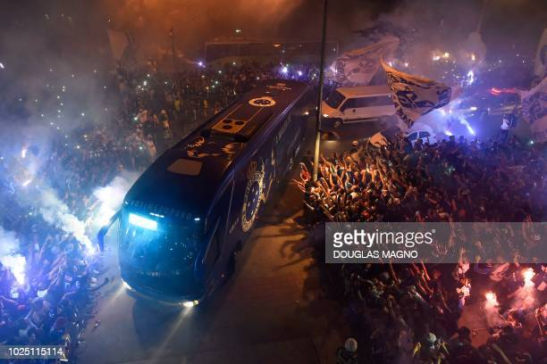 The bus transporting the players of Brazil's Cruzeiro is surrounded by supporters before their 2018 Copa Libertadores football match against Brazil's...
