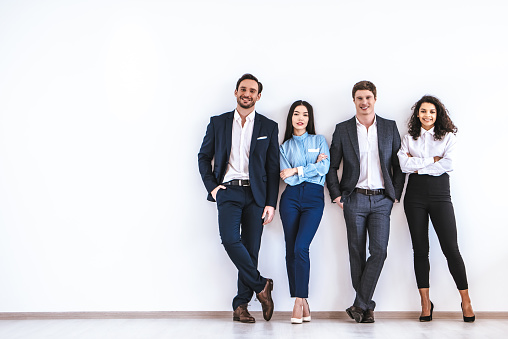 The business people standing on the white wall background 986662156