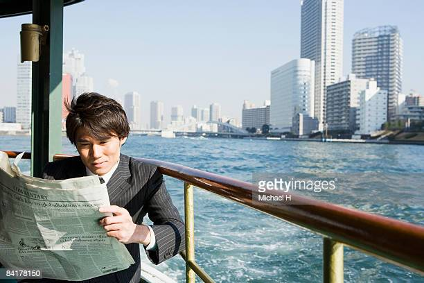 The businessman who reads a newspaper by ship