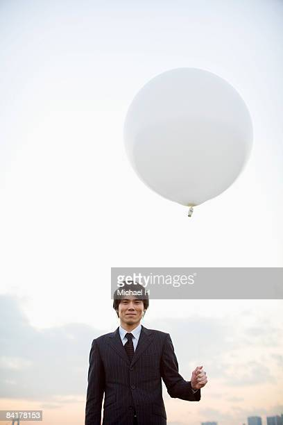 The businessman who stands with a balloon