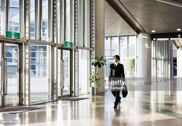 the businessman who walks the office building - 建物入口 ストックフォトと画像