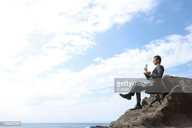 The businessman with cup of coffee on the cliff.